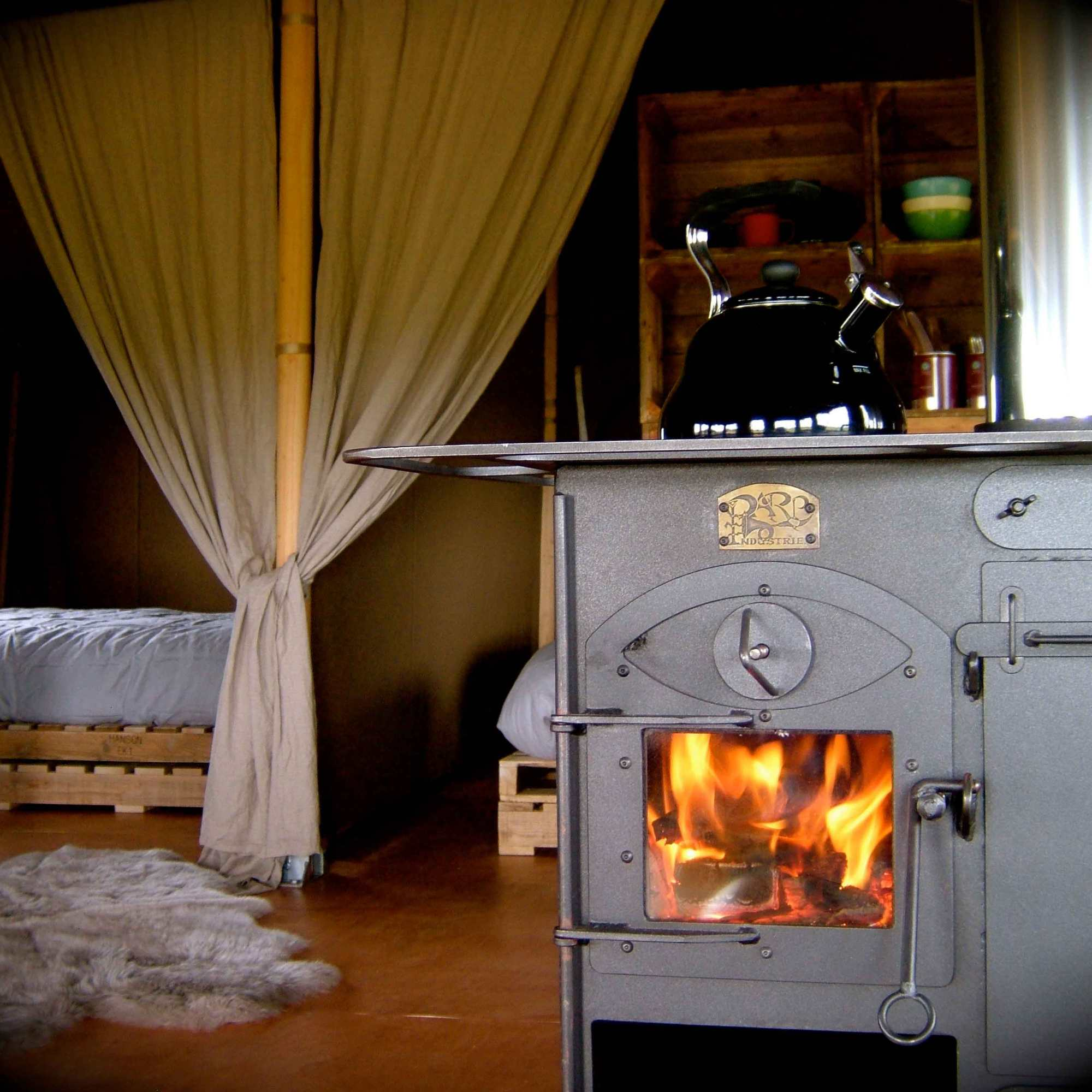 the whistling kettle on the wood stove in Woody safari tent