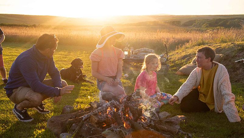 family toasting marshmallows round the firepit