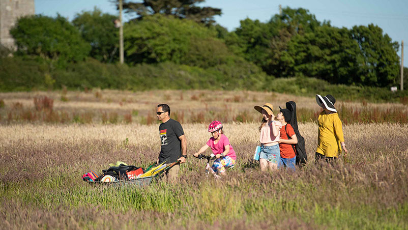Glampers arriving with wheelbarrow walking through the long grass in the meadow