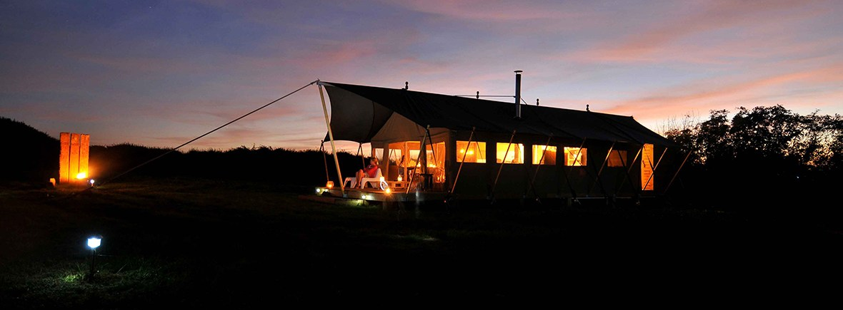 a safari tent at night with the sunset and cosy glow of the lanterns