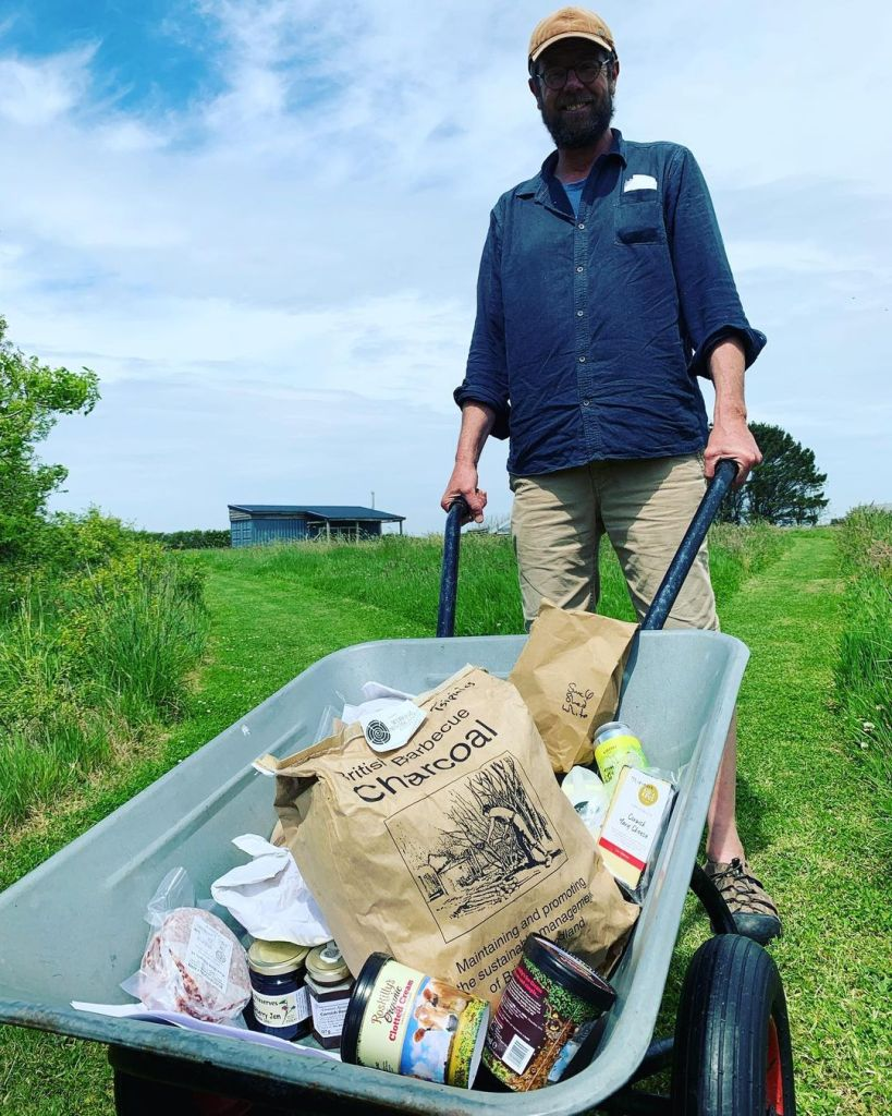 a wheelbarrow of local food delivered to barefoot glamping