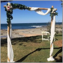 Weddng arbour with white chiffon & decorated with green ivy and peonies. Shelley Beach, Sunshine Coast.