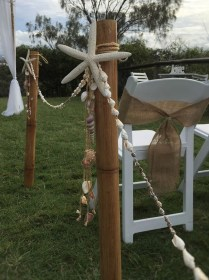 Bamboo aisle poles with shell & starfish decor.