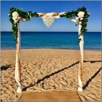 Bamboo wedding arbour styled with white chiffon, green ivy, faux flowers & white wicker love heart - Kawana Beach