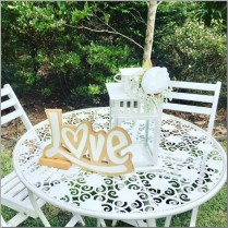 Round vintage wedding signing table styled with love sign & white lantern & faux flowers.