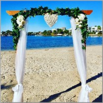 Timber wedding arbour styled with white chiffon curtains, wicker love heart & faux green ivy & flowers. Double Bay Beach, Kawana Island.