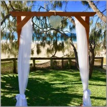 Timber wedding arbour styled with white chiffon & love heart. Hidden Grove, Noosa.
