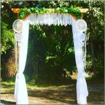 Timber wedding arbour styled with lace curtains, lace garland, dreamcatchers & ivy. Pelican Waters, Sunshine Coast.
