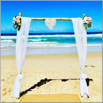 Bamboo wedding arbour styled with white chiffon, pink & white faux flowers & wicker love heart. Buddina Beach, Sunshine Coast.