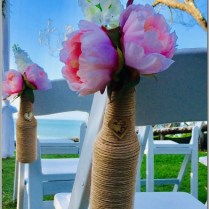 Jute string bottles styled with pink and white faux flowers. Casuarina Gardens, Noosa.