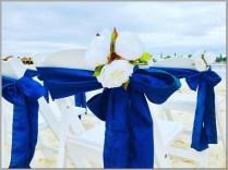 White peony posies with navy blue chair sashes. Aisle decor.