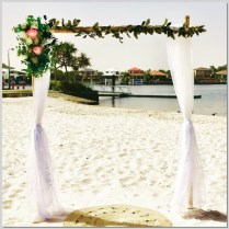 Bamboo wedding arch styled with chiffon and faux native flowers & greenery. Mykies By The Bay, Kawana Island.
