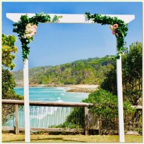 White timber wedding arbour styled with faux greenery & pink & white peoy flowers. Point Perry Lookout, Coolum.