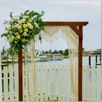Timber wedding arch styled with macrame hanging & fresh flowers. Mooloolaba, Sunshine Coast.