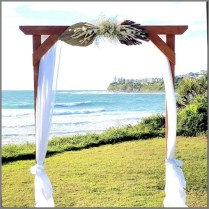 Timber wedding arch styled with white chiffon and dried palm leaf and flower arrangment. Caloundra, Sunshine Coast