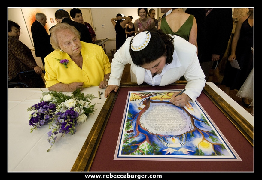 Rebecca signs the ketubah, as her grandmother witnesses. The ketubah is the jewish marriage contract which is signed prior to the ceremony.