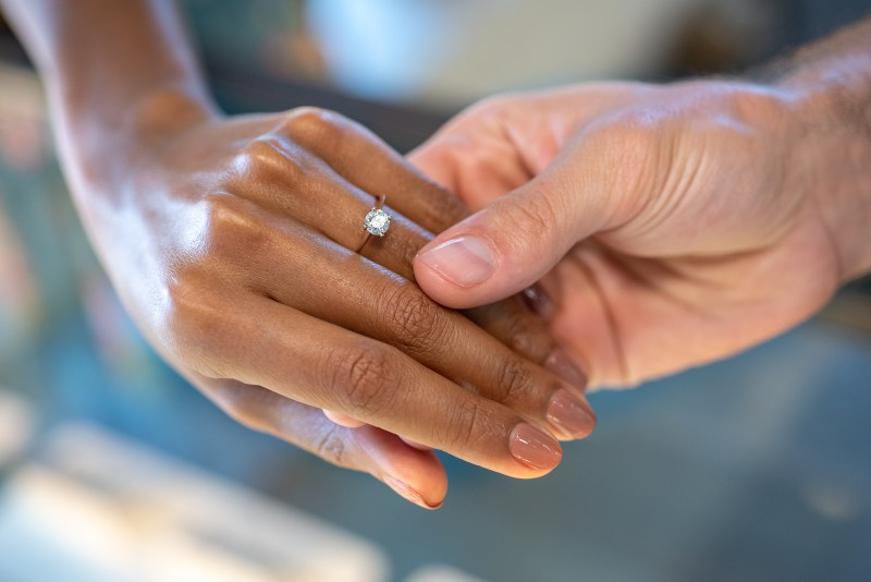 Photograph of two hands holding with one hand wearing a diamond engagement ring