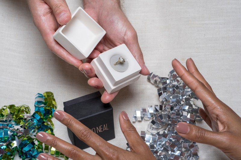 Photograph of a man holding a jewelry box with an engagement ring inside