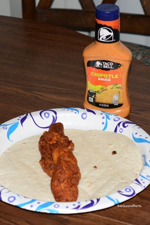 Chicken strips on a tortilla shell on a plate with chipotle sauce in a bottle next to it.