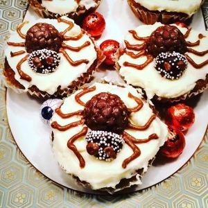 Cupcakes decorated with white frosting and a candy spider
