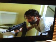 """As Rick grabs the man's gun and prepares to go out the bathroom window, he goes back to crack the door of the bathroom open, to set a """"walker time bomb"""" onto the Downstairs Thug Boys once the dead guy reanimates...tactical genius, Rick Grimes-style!"""