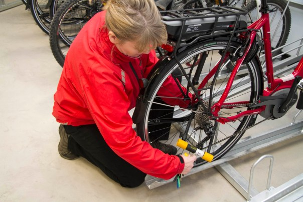 Cyclist locking her bike at the Barnsley Bike Hub