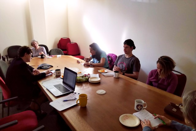 Image. Photo B from Elections Canada Tele Town Hall Event Held June 6th 2019. Several people sit around a large wooden conference table with a large triangular tele-conference phone in the center of the table.