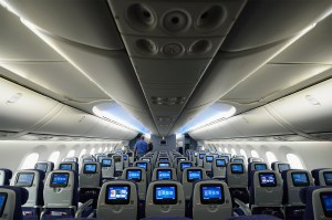 Image. Inside of a large airliner. Empty. Rows and rows of seats placed tightly together as far as the eye can see.