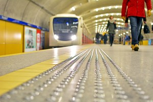 Photo of a close up of tactile metal guide strips embedded into the floor of a train station next to a bright yellow line. A train is pulling up in the distance. People all throughout the background of the photo are preparing to board.