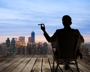 A dark silhouette of a businessman sitting on a chair holding a cigar and looking out over the city at night.