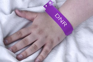 A hand laying on a medical bed wears a purple tag that reads DNR.