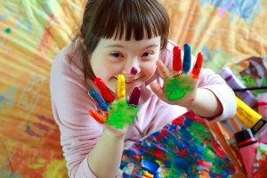 A beautiful little girl with Down Symdrome smiles while looking up at the camera with painted hands. Each finger a different color. A small splotch of paint on her nose. A desk full of different colored paints beneath her.
