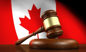 Gavel on a wooden desktop with a Canadian flag in the background.