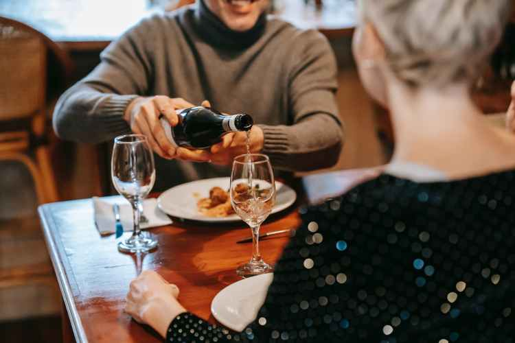 anonymous couple having date with wine and food in restaurant