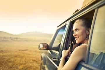 cheerful woman in car enjoying sunset