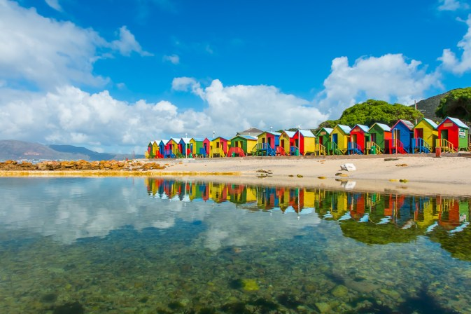 Colourful huts reflected in the St James beach tidal pool