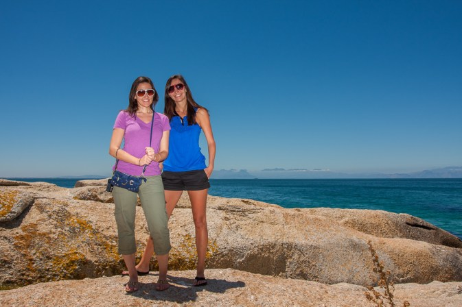 Two gorgeous girls pose on the rocks overlooking the sea