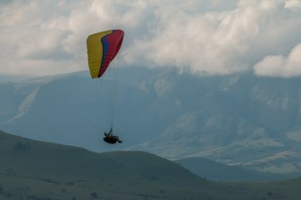 A lone paraglider sores over a cloudy valley