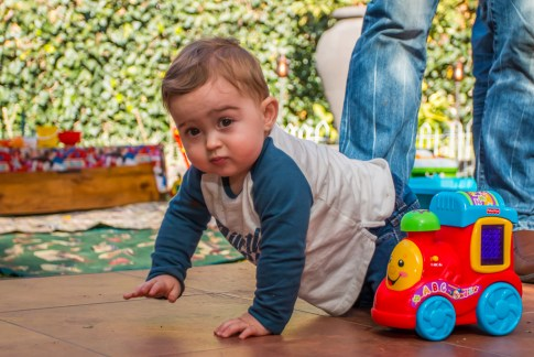 A one year old crawling next to his toy train