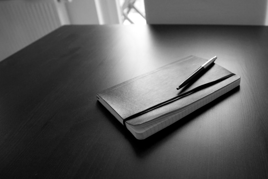 Closed notebook with a pen on top laying on top of a desk