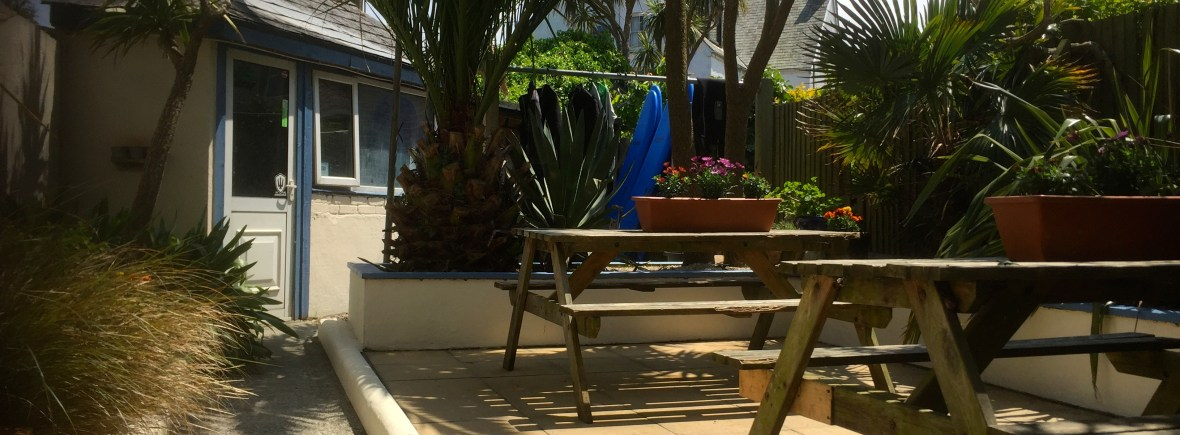 Tropical Garden at Base Surf Lodge. Palm Trees, sunshine and picnic benches.