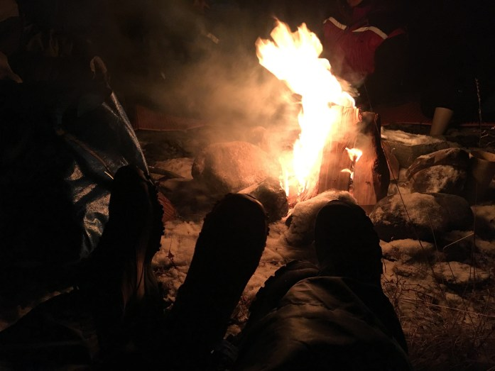 warming our feet by the fire on the northern lights chase tour