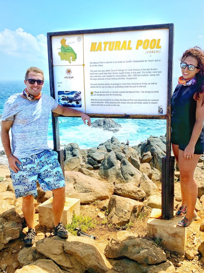 Couple posing with Natural Pool sign on rocks and the ocean in the background.
