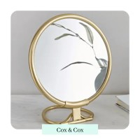 Circular brass french vanity mirror on a marble surface by cox and cox