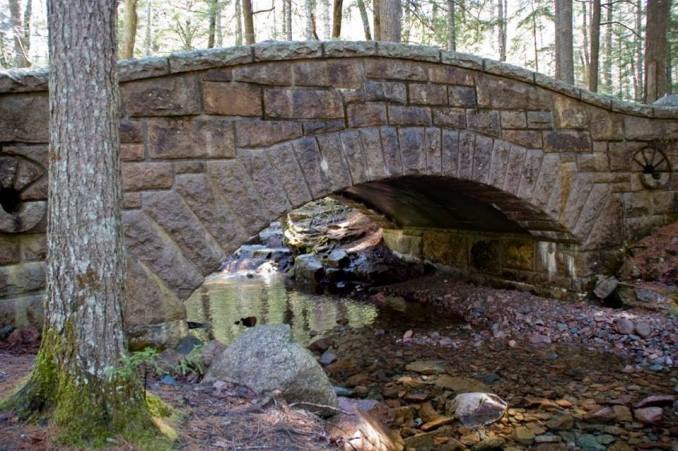 Image of Hadlock Bridge in Acadia National Park; an arched stone bridge with a small creek flowing beneath the bridge.