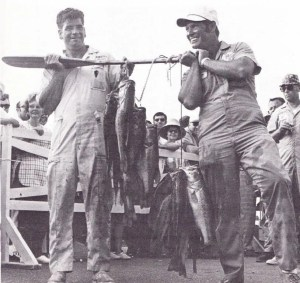 1970 Bass Master Trail. Charles Redding (left) and Joe Kennedy (right) bring their fish to the scales with the aid of a boat paddle. Photo Summer 1970 issue of Bassmaster Magazine.