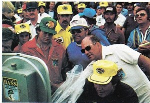 Daves waits patiently as Tournament Director Harold Sharp reads the weight. Photo Sept/Oct 1975 Issue of Bassmaster Magazine.