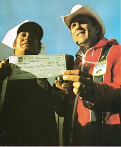 Ray Scott presents Jack Hains with the $15,000 winners check after winning the 1975 Bassmaster Classic on Currituck Sound. Photo February 1976 issue of Bassmaster Magazine.
