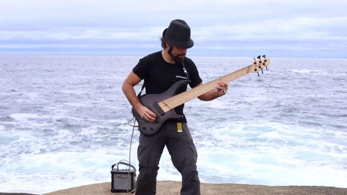 波打ち際でベースを弾くフェリペ・ゴメスさん