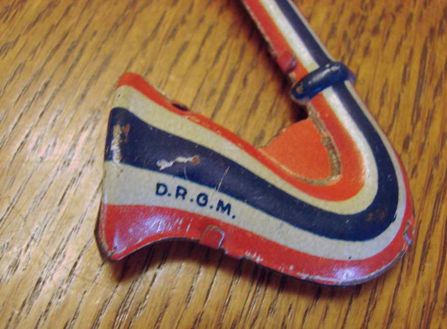 German, tri-coloured tin toy, saxophone-shaped, vintage musical toy